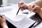 Ořezaný pohled na starší páry držící pero a dokumenty s nápisem vymáhání pohledávek doma