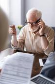 Selektivní zaměření člověka mluvení na smartphone v blízkosti papíry a gadgets na stole