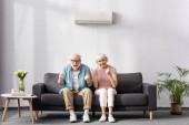 Veselý starší pár ukazuje palce nahoru a jo gesta na pohovce doma