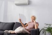 Selektiver Fokus einer älteren Frau, die auf der Couch im Wohnzimmer sitzt und mit einem Ventilator wedelt