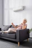 Ältere Frau wedelt mit Ventilator unter Klimaanlage im Wohnzimmer
