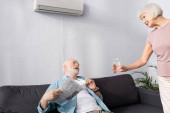 Starší žena dává sklenici vody manželovi drží noviny pod klimatizací doma