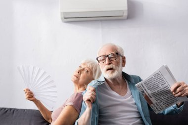 Senior man holding newspaper near tired wife with fan under air conditioner in living room stock vector
