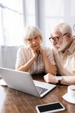 Selective focus of elderly couple looking at laptop near smartphone and coffee on table stock vector