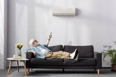 Cheerful senior man using remote controller of air conditioner while sitting on couch stock vector