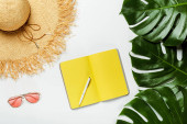 top view of green palm leaves, straw hat, sunglasses and yellow notepad on white background