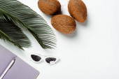 top view of green palm leaves, sunglasses, coconuts and notepad on white background