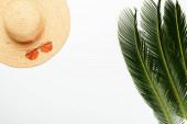 vrchní pohled na zelené palmové listy v blízkosti slaměný klobouk a sluneční brýle na bílém pozadí