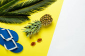 top view of green palm leaves, pineapple, sunglasses and blue flip flops on white and yellow background