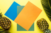 top view of green palm leaves and ripe pineapples on colorful background