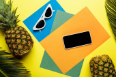 top view of green palm leaves, sunglasses, smartphone and ripe pineapples on colorful background