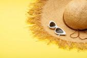 slaměný klobouk a stylové brýle na žlutém pozadí