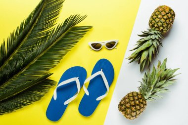 Top view of green palm leaves, pineapples, sunglasses and blue flip flops on white and yellow background stock vector