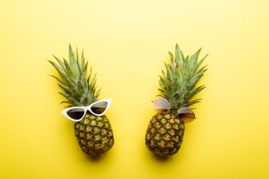 Top view of ripe pineapples in sunglasses on yellow background stock vector