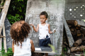 selective focus of poor african american kid standing near chalkboard with lettering and curly sister