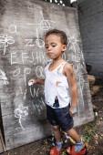 Africké americké dítě v roztrhaných šatech držící křídu u tabule