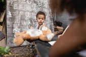 selektivní zaměření afrického amerického chlapce držícího měkkou hračku v blízkosti dětí a tabulí