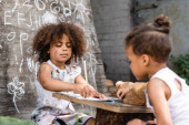 selective focus of poor african american kid writing in notebook near brother outside