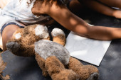 Photo cropped view of poor african american kid near teddy bear and notebook on desk