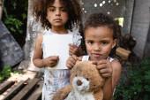 selektivní zaměření chudého afrického amerického kluka držícího prázdný papír a tužku poblíž bratra s plyšovým medvědem