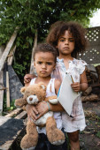 poor african american kid holding blank paper and pencil while standing near sad brother with teddy bear