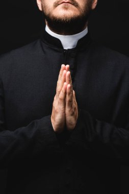 Cropped view of priest with praying hands isolated on black stock vector