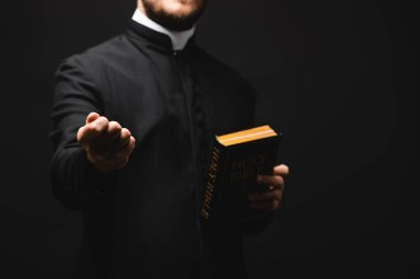 Cropped view of priest holding holy bible while showing fist isolated on black stock vector