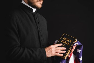 Partial view of priest holding holy bible and american flag isolated on black stock vector