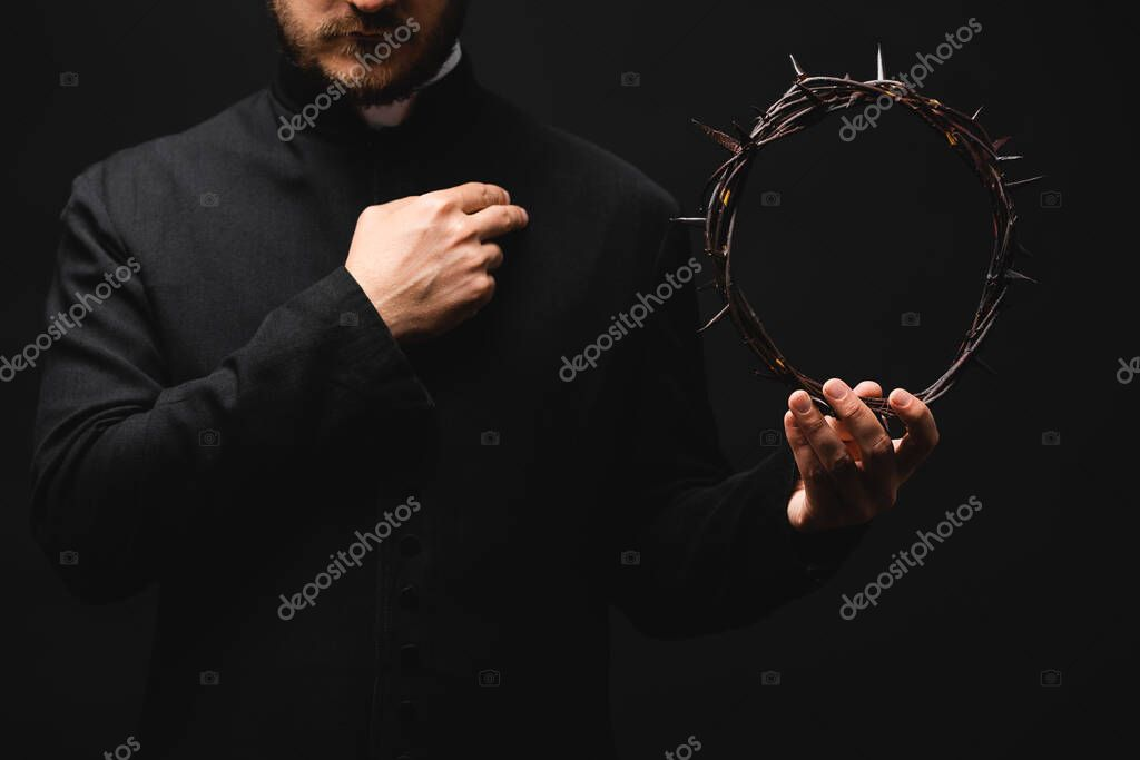 Cropped view of priest holding wreath with spikes in hand while praying isolated on black stock vector