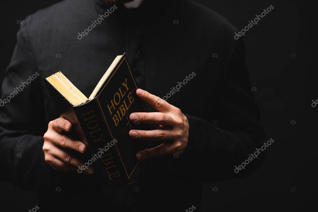 Partial view of pastor holding holy bible in hands isolated on black stock vector