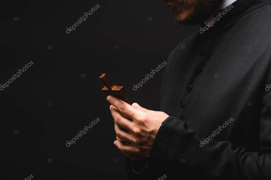 Cropped view of priest holding cross isolated on black stock vector