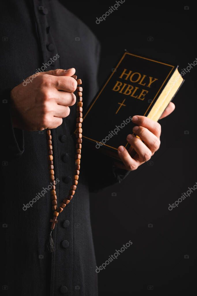 Cropped view of priest holding holy bible and rosary beads in hands isolated on black stock vector