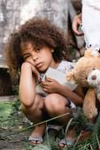 Verärgertes und armes afrikanisches Kind hält Notizbuch neben Kind, das mit schmutzigem Teddybär steht