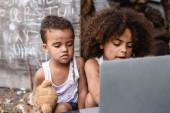 selektivní zaměření chudých afrických amerických dětí při pohledu na notebook venku