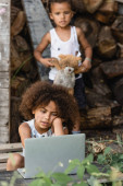Selective focus of african american kid sitting near laptop and brother with teddy bear in slum