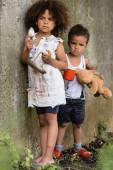 Selektiver Fokus obdachloser afrikanisch-amerikanischer Kinder mit Teller und Tasse beim Betteln um Almosen im Slum