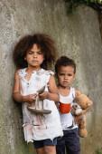 Verzweifelte afrikanisch-amerikanische Kinder mit Teller und Löffel blicken in die Kamera, während sie in der Nähe einer Betonmauer auf der Stadtstraße Almosen erbetteln