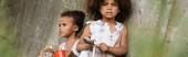 Panoramaorientierung afrikanisch-amerikanischer Kinder beim Betteln um Almosen in der Nähe einer Betonmauer im Slum