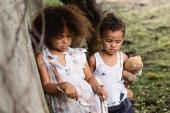 Selektiver Fokus hilfloser afrikanisch-amerikanischer Kinder mit Löffel, Tasse und Teddybär, die in der Nähe einer Betonmauer auf der städtischen Straße stehen