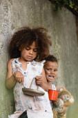 Selektiver Fokus armer afrikanisch-amerikanischer Kinder mit Metalllöffel und Teller in der Nähe des Bruders, der im Slum Almosen erbettelt