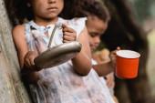 Selektiver Fokus armer afroamerikanischer Kinder, die auf städtischen Straßen um Almosen betteln
