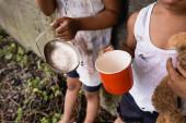 Ausgeschnittene Ansicht obdachloser afrikanisch-amerikanischer Kinder mit Tasse und Metallteller beim Betteln um Almosen auf der städtischen Straße