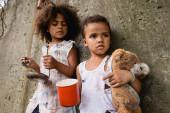 Selektiver Fokus armer afrikanisch-amerikanischer Junge mit schmutzigem Teddybär beim Betteln um Almosen in der Nähe der Schwester auf der Straße