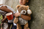 Photo Cropped view of homeless african american children with dirty teddy bear begging alms in slum