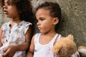 Selective focus of poor african american kids in messy clothes with teddy bear standing near concrete wall on urban street