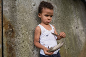 Trauriger mittelloser afrikanischer Junge mit Metallteller und Löffel beim Betteln um Almosen auf urbaner Straße