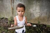 Nespokojený africký americký chlapec drží špinavou talíř a lžíci a dívá se na kameru na městské ulici