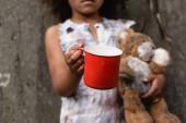 Ausgeschnittene Ansicht des armen afrikanisch-amerikanischen Kindes mit Metallbecher und Teddybär beim Betteln um Almosen auf der städtischen Straße