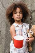 Selektiver Fokus armer afrikanisch-amerikanischer Kinder mit Teddybär und Metallbecher für Almosen auf städtischen Straßen