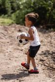 Boční pohled na deprivitute africký americký chlapec drží fotbalový míč na špinavé silnici ve slumu